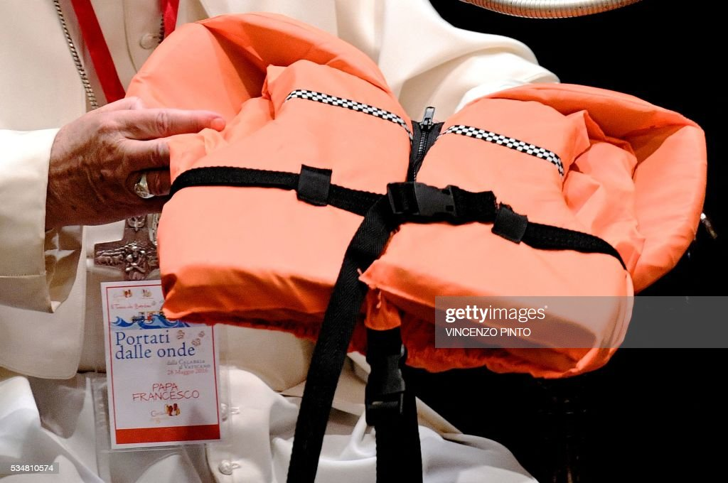 Pope Francis shows the life jacket of a young victim drowned in the Mediterranean sea trying to reach Europe on May 28, 2016 at the Vatican during a meeting with 400 children from the south of Italy, Calabria, including children of migrants. The life jacket was donated to him by a rescuer during the last general audience in Vatican on May 25, 2016. / AFP / Vincenzo PINTO