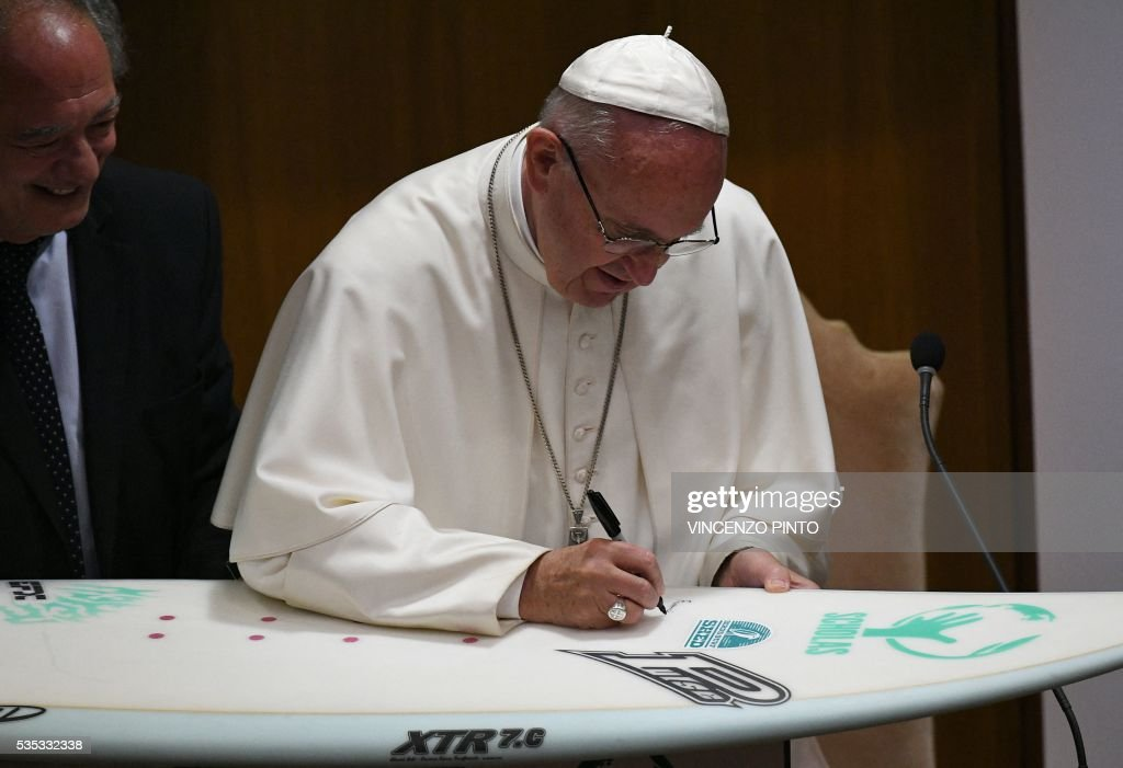 Pope Francis signs a surf board during a meeting with the participants of the Sixth World Congress of Pontifical Foundation Scholas, on May 29, 2016 in Vatican. Scholas is an international organization of pontifical right approved and created by Pope Francis in Vatican City August 13, 2013. It combines technology with art and sport to promote social integration and culture of encounter for peace. / AFP / VINCENZO
