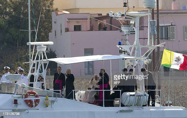 Pope Francis sits on a boat of the coast guards on his way to cast a wreath during his visit to the island of Lampedusa a key destination of tens of...