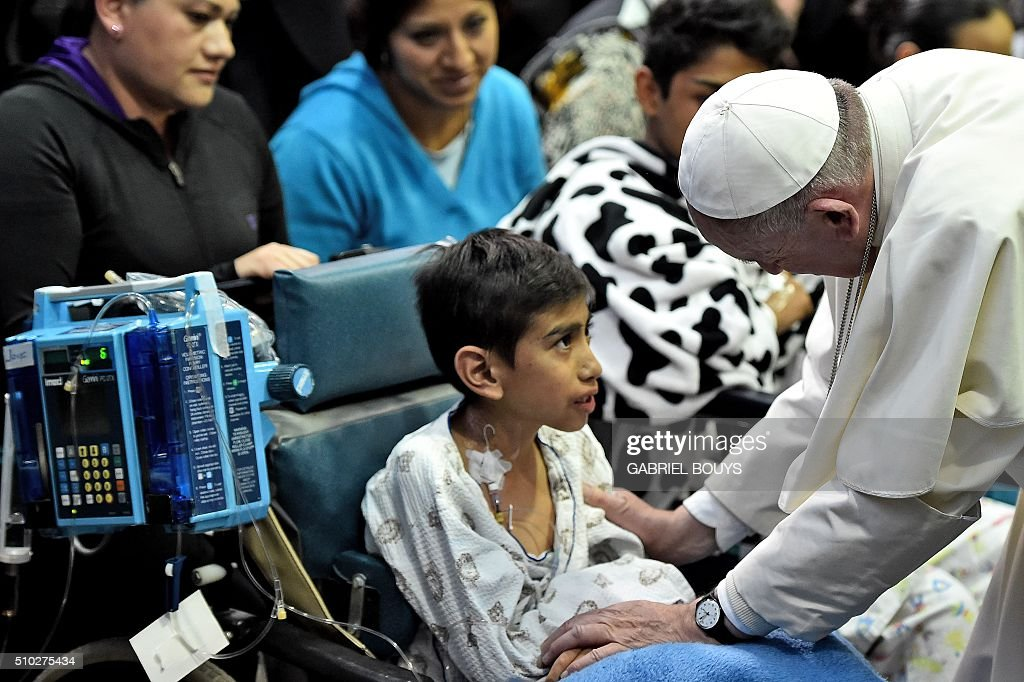 Pope Francis speaks with a child during his visit to the Federico Gómez children's hospital in Mexico on February 14, 2016.Pope Francis celebrated an open-air mass with 300,000 Catholic faithful in a crime-plagued Mexican city on Sunday, urging them to create a country free of emigration and 'merchants of death.' AFP PHOTO / GABRIEL BOUYS / AFP / GABRIEL BOUYS