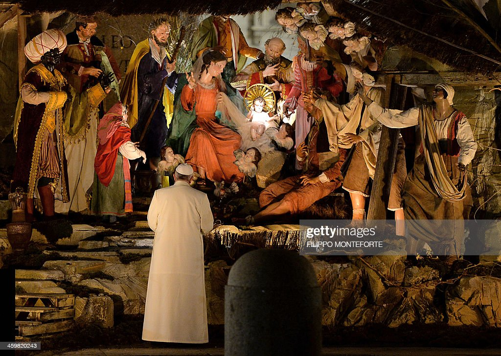 Pope Francis stands in front of a Nativity scene in St Peter's square at the Vatican on December 31, 2013. AFP PHOTO / FILIPPO MONTEFORTE
