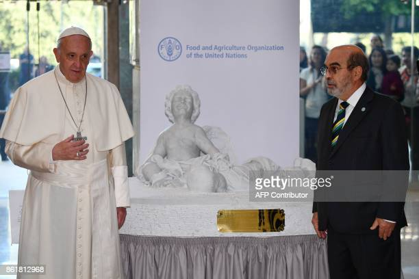 Pope Francis stands next to a sculpture donated by him to the Food and Agriculture Organization of the United Nations in presence of FAO general...