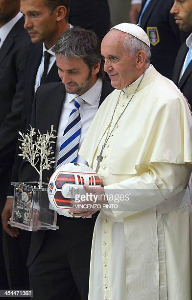 Pope Francis stands next to Argentinian craftsman Adrian Pallarols as he poses for the family photo with international football players at the...