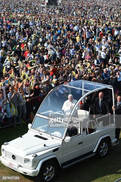 Pope Francis stands on the popemobile as he arrives to celebrate a mass in the park of Monza as part of a one day visit in Milan on March 25 2017 /...
