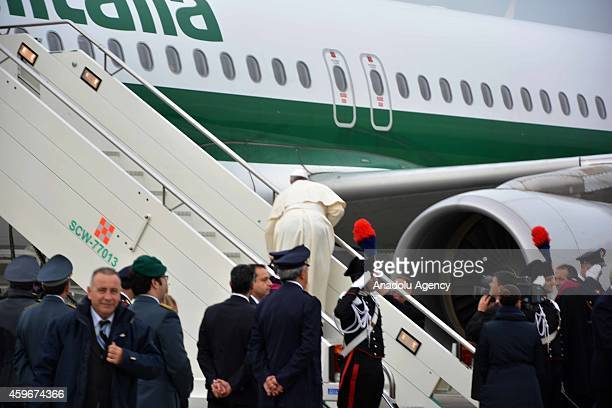 Pope Francis stumbles as he embarks a plane for a threeday visit to Turkey at Fiumicino international airport on November 28 2014 in Rome Italy...