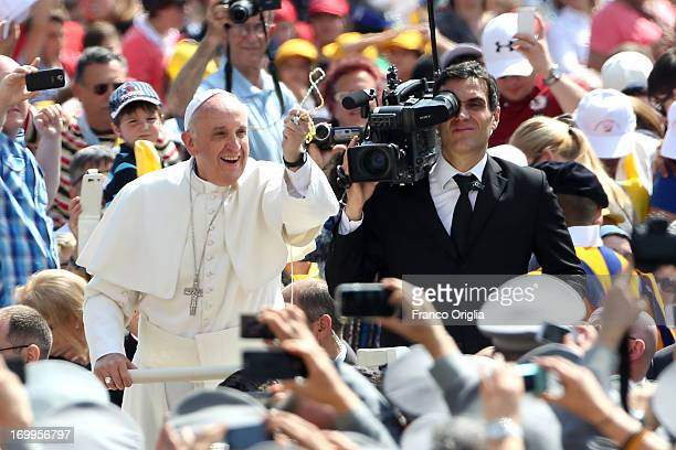 Pope Francis takes a rosary from a faithful as he arrives on popemobile in St Peter's Square for his weekly audience on June 5 2013 in Vatican City...