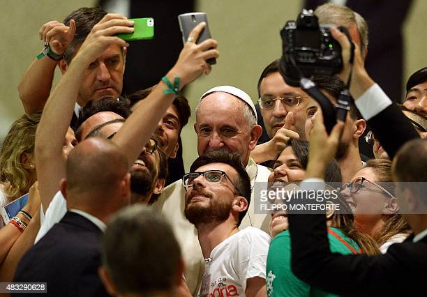 Pope Francis takes a selfie with a group of people during a meeting with the Youth Eucharistic Movement in the Paul VI hall at the Vatican on August...