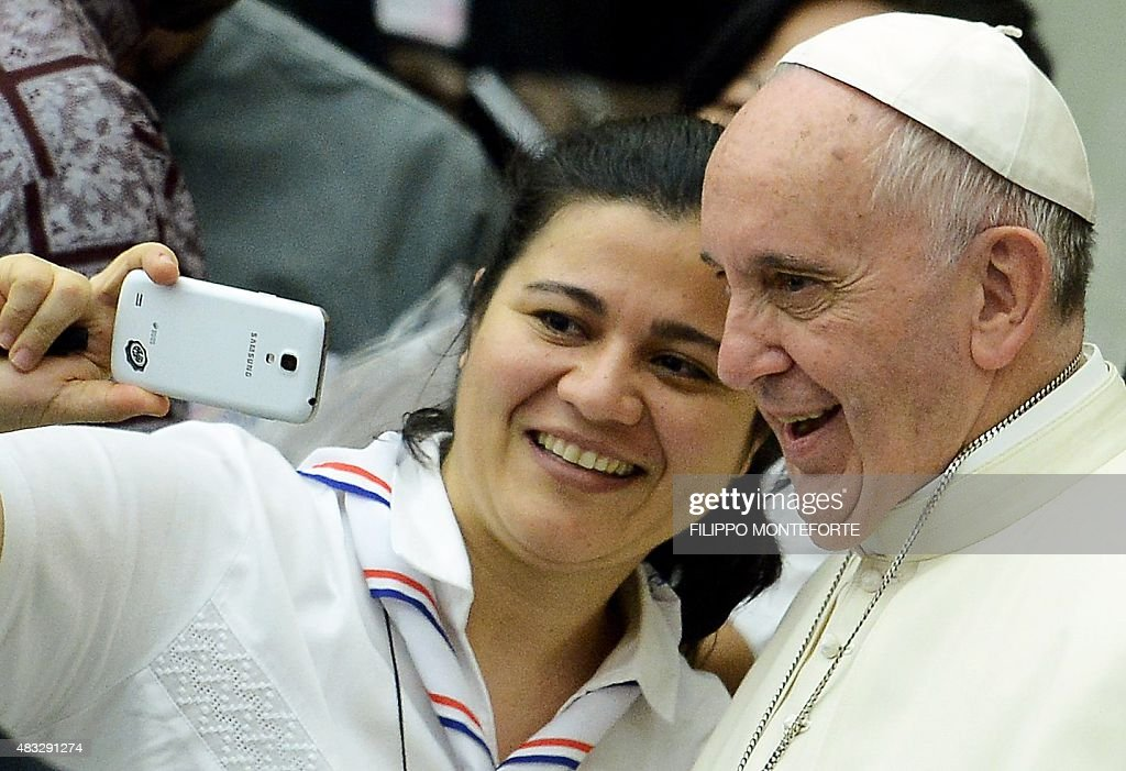 Pope Francis takes a selfie with a woman during a meeting with the Youth Eucharistic Movement in the Paul VI hall at the Vatican on August 7 2015 AFP...