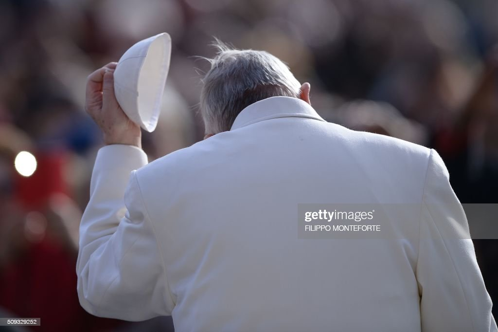 Pope Francis takes off his skullcalp during his weekly general audience on February 10, 2016 at St Peter's square in Vatican. / AFP / FILIPPO MONTEFORTE