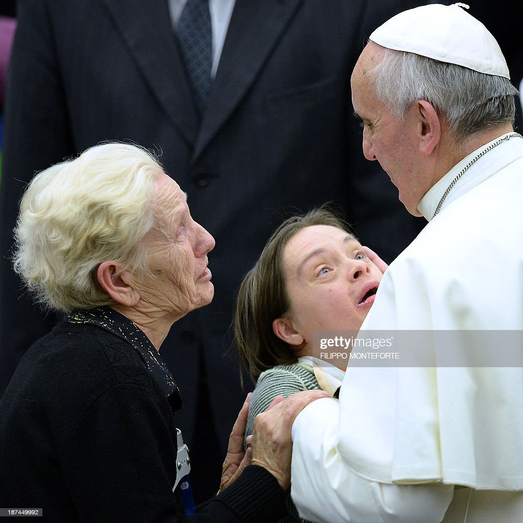 Pope Francis talks on November 9, 2013 with disabled people during a meeting with the UNITALSI, Italian Union for the transportation of sick people to Lourdes and International Shrines in the Paul VI hall at the Vatican. AFP PHOTO/Filippo MONTEFORTE