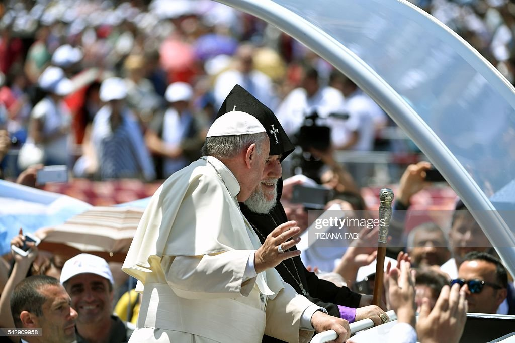Pope Francis talks to Catholicos of All Armenians Karekin II as they ride on the popemobile through the crowd of faithful after an open-air mass in Armenia's second-largest city of Gyumri on June 25, 2016. / AFP / TIZIANA
