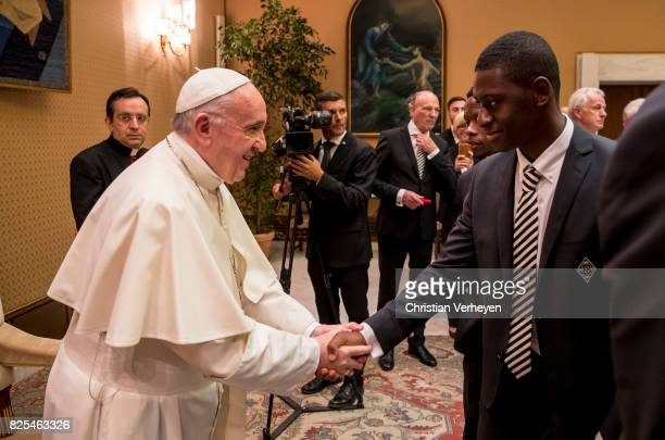 Pope Francis talks to Mamadou Doucoure during a private audience with his team of Borussia Moenchengladbach in the Palace of the Vatican on August 02...