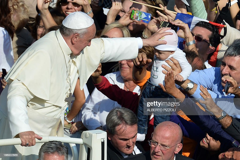 Pope Francis touches the head of a baby as he greets the crowd at St Peter's square after a mass on the occasion of the Family Days on October 27, 2013 at the Vatican. AFP PHOTO / ALBERTO PIZZOLI