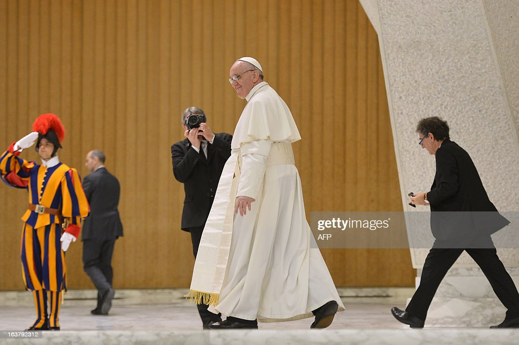 Pope Francis walks during a private audience of the pope to members of the media on March 16, 2013 at the Paul VI hall at the Vatican. Pope Francis on Saturday called for 'a poor Church for the poor', saying he chose his papal name because St Francis of Assisi was 'a man of poverty and a man of peace'.
