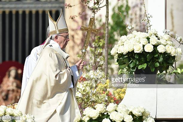 Pope Francis walks past flowers during the Easter Sunday mass on March 27 2016 at St Peter's square in Vatican Christians around the world are...