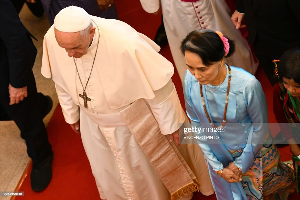 Pope Francis (L) walks with Myanmar's civilian leader Aung San Suu Kyi in Naypyidaw on November 28, 2017. Pope Francis called for respect for rights and justice in a keenly-watched address in Myanmar on November 28, but refrained from any mention of the Rohingya, or allegations of ethnic cleansing that has driven huge numbers of the Muslim minority from the country. / AFP PHOTO / Vincenzo PINTO