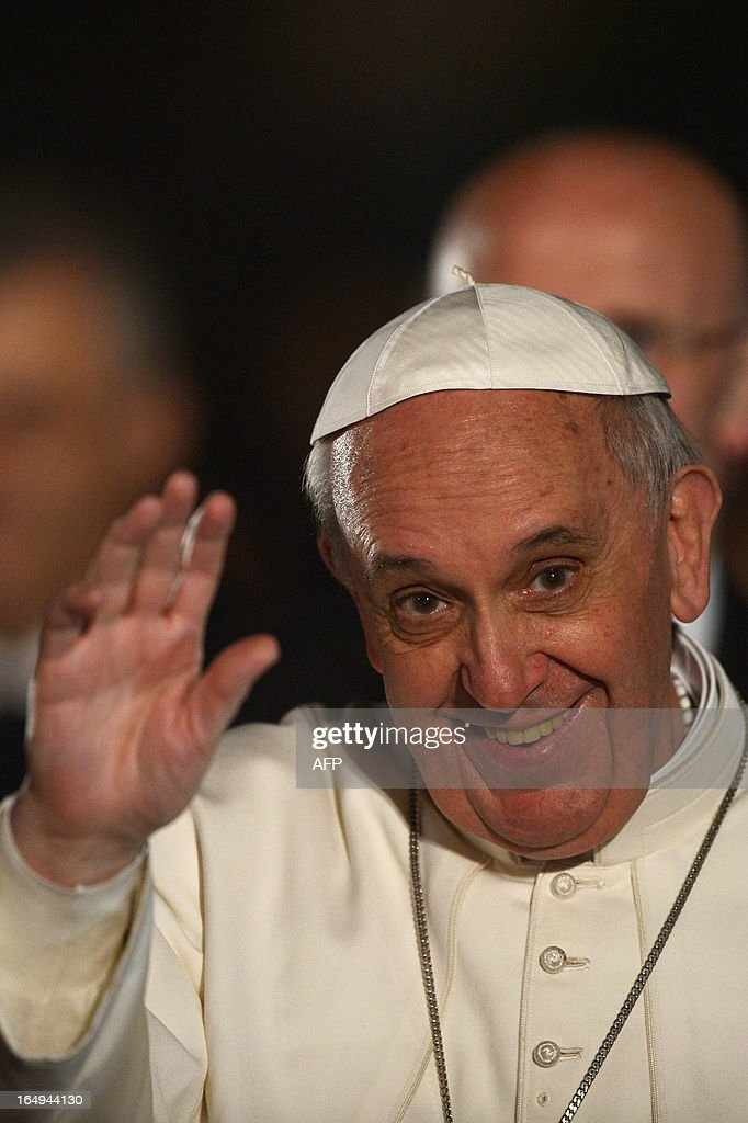 Pope Francis waves after the celebration of the Way of the Cross on Good Friday on March 29, 2013 at the Colosseum in Rome. Pope Francis presided over his first Good Friday which will culminate in a torch-lit procession at Rome's Colosseum and prayers for peace in a Middle East 'torn apart by injustice and conflicts'. AFP PHOTO / GABRIEL BOUYS