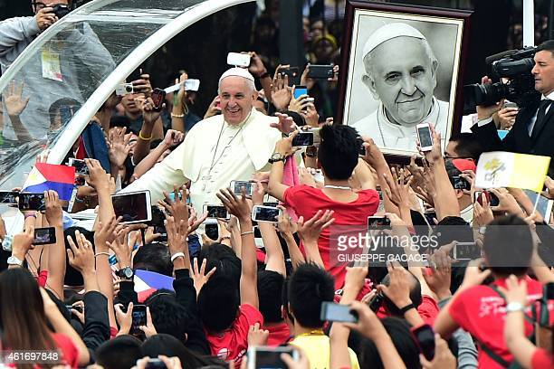 Pope Francis waves as he arrives for a meeting with youths at the University of Santo Tomas in Manila on January 18 2015 Pope Francis will celebrate...
