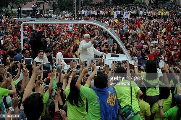 Pope Francis waves as he arrives for a visit to the University of Santo Tomas in Manila on January 18 2015 Pope Francis will celebrate mass with...