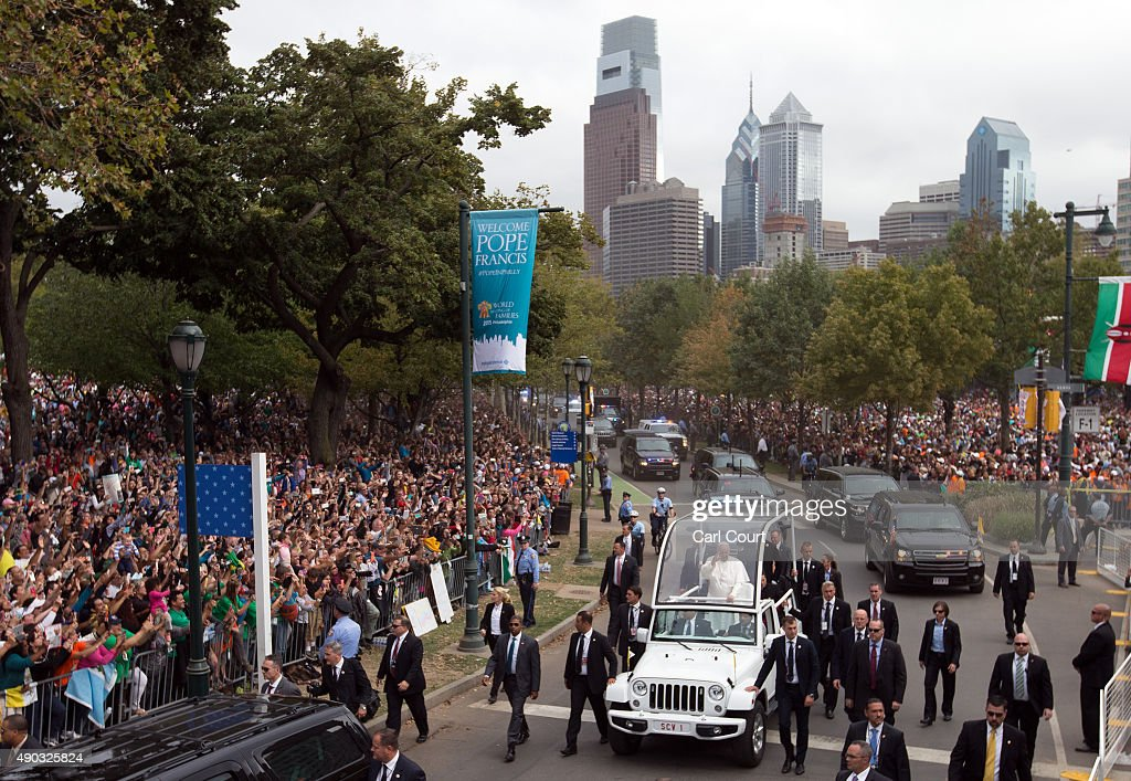 Pope Francis waves as he drives along Benjamin Franklin Parkway to lead Mass on September 27, 2015 in Philadelphia, Pennsylvania. Pope Francis is on the final day of his trip to the United States and will conduct Mass and meet with organizers, volunteers and benefactors of the World Meeting of Families before returning to Rome this evening.