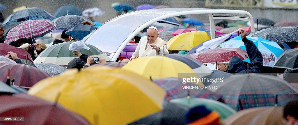Pope Francis waves at pilgrims gathered at Saint Peter's square in the Vatican, upon his arrival to lead the general weekly audience on February 5, 2014.