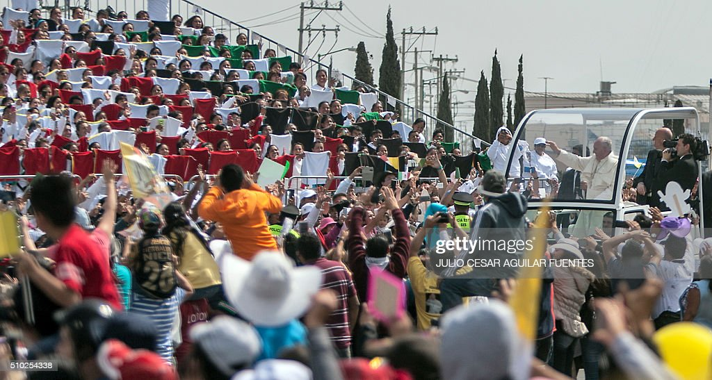 Pope Francis waves at the crowd from the Popemobile after celebrating an open-air mass in Ecatepec, near Mexico City on February 14, 2016. Pope Francis urged Mexicans on Sunday to turn their country into a land of opportunity where there is no need to emigrate or mourn victims 'of the merchants of death.'. AFP PHOTO/ JULIO CESAR AGUILAR / AFP / Julio Cesar Aguilar Fuentes
