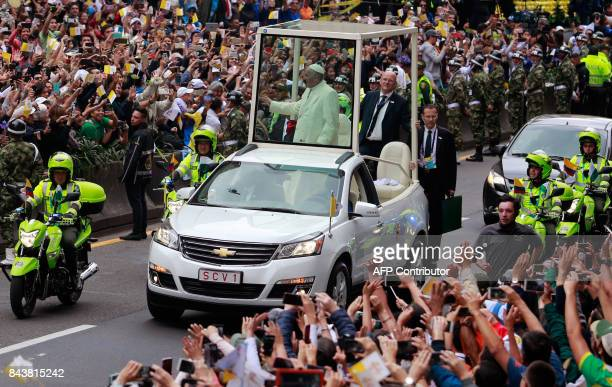 Pope Francis waves at the crowd from the popemobile as he goes from the Archbishop's Palace at Bolivar Square to the Nunciature in Bogota on...