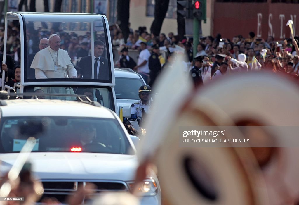 Pope Francis waves at the crowd from the popemobile on his way to the Guadalupe Basilica in Mexico City on February 13, 2016. Pope Francis urged Mexican bishops Saturday to take on drug trafficking with 'prophetic courage,' warning that it represents a moral challenge to society and the church. AFP PHOTO/ JULIO CESAR AGUILAR / AFP / Julio Cesar Aguilar Fuentes