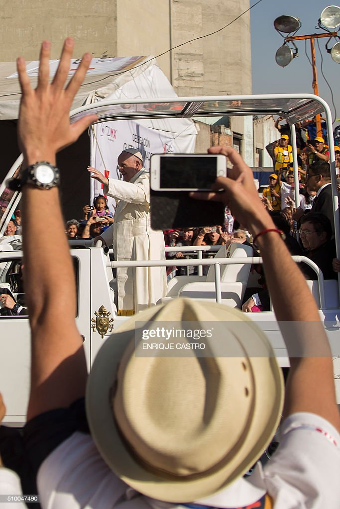 Pope Francis waves at the crowd from the popemobile on his way to the Guadalupe Basilica, in Mexico City on February 13, 2016. AFP PHOTO/ENRIQUE CASTRO / AFP / ENRIQUE CASTRO