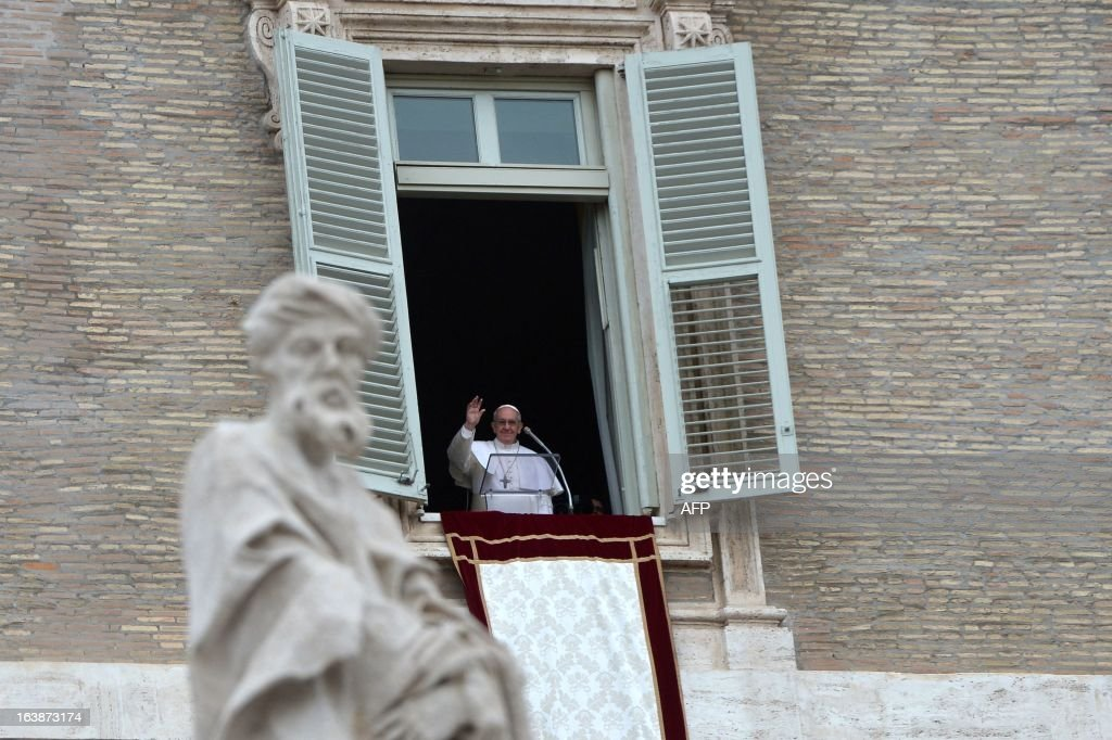 Pope Francis waves at the window as he leads the Angelus prayer at St Peter's square on March 17, 2013 at the Vatican. Pope Francis begins his papacy in earnest today ahead of his formal inauguration mass, with a weekly prayer address used by previous pontiffs to comment on international affairs. The pope's first Angelus prayer, delivered from a window high above St Peter's Square, is a chance for the first Latin American pontiff to begin to sketch out a more global vision for the role of the Roman Catholic Church. AFP PHOTO / GABRIEL BOUYS