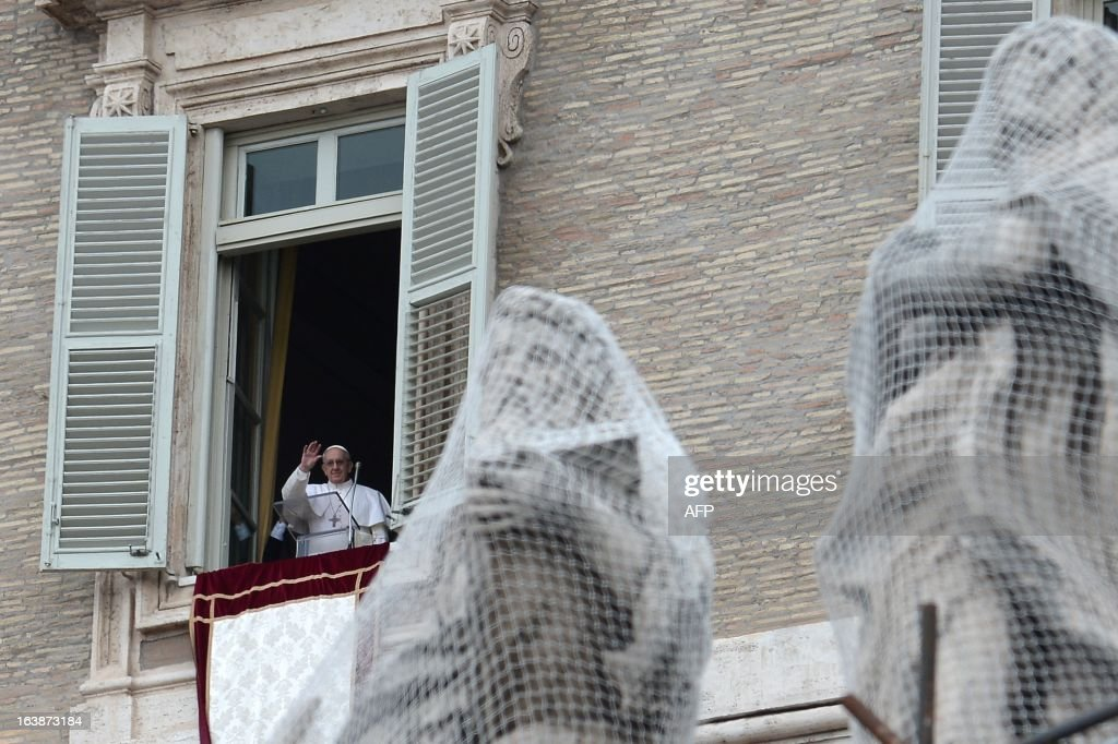 Pope Francis waves at the window as he leads the Angelus prayer at St Peter's square on March 17, 2013 at the Vatican. Pope Francis begins his papacy in earnest today ahead of his formal inauguration mass, with a weekly prayer address used by previous pontiffs to comment on international affairs. The pope's first Angelus prayer, delivered from a window high above St Peter's Square, is a chance for the first Latin American pontiff to begin to sketch out a more global vision for the role of the Roman Catholic Church. AFP PHOTO / FILIPPO MONTEFORTE