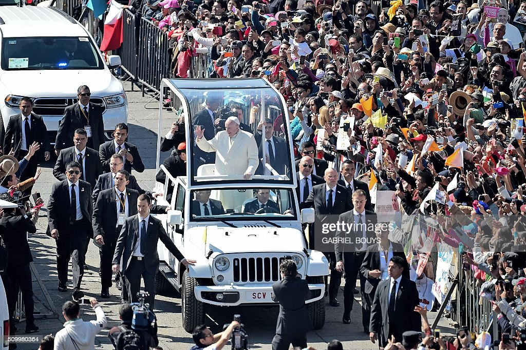 Pope Francis waves from the popemobile on his way to the cathedral, in Mexico City on February 13, 2016. Francis became the first pope to enter Mexico's National Palace to meet President Enrique Pena Nieto, as he starts a cross-country tour that will highlight the country's violence and migration troubles. AFP PHOTO/GABRIEL BOUYS / AFP / GABRIEL BOUYS