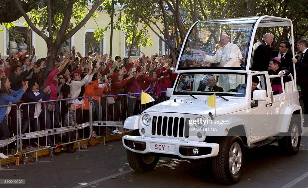 Pope Francis waves from the popemobile on his way to the Guadalupe Basilica, in Mexico City on February 13, 2016. AFP PHOTO/DIANA ULLOA / AFP / DIANA ULLOA