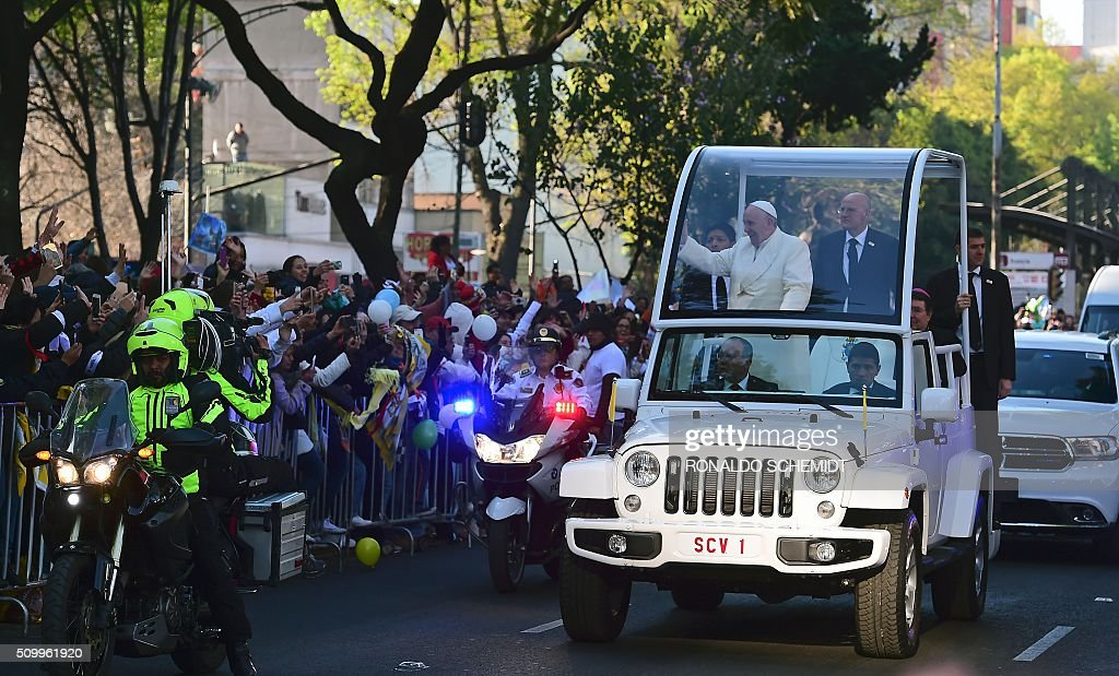 Pope Francis waves from the popemobile on his way to the National Palace, in Mexico City on February 13, 2016. Francis will be the first pope to enter Mexico's National Palace to meet President Enrique Pena Nieto, as he starts a cross-country tour that will highlight the country's violence and migration troubles. AFP PHOTO / RONALDO SCHEMIDT / AFP / RONALDO SCHEMIDT