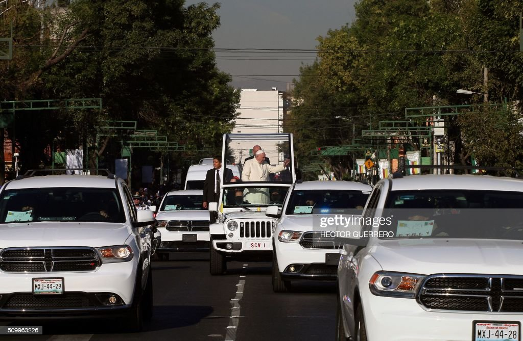 Pope Francis waves from the popemobile on his way to the National Palace, in Mexico City on February 13, 2016. Francis will be the first pope to enter Mexico's National Palace to meet President Enrique Pena Nieto, as he starts a cross-country tour that will highlight the country's violence and migration troubles. AFP PHOTO / HECTOR GUERRERO / AFP / HECTOR GUERRERO