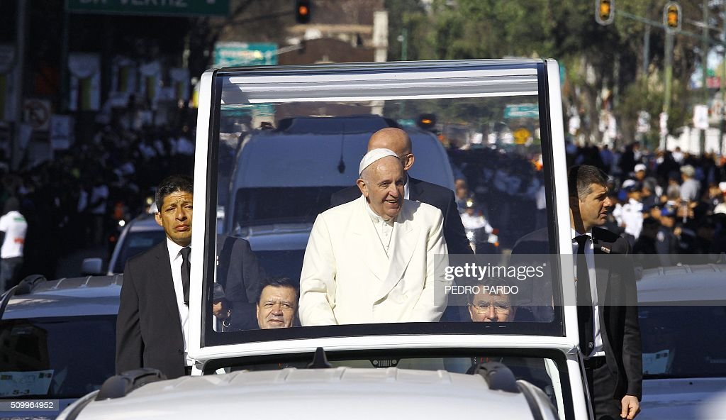 Pope Francis waves from the popemobile on his way to the National Palace, in Mexico City on February 13, 2016. Francis will be the first pope to enter Mexico's National Palace to meet President Enrique Pena Nieto, as he starts a cross-country tour that will highlight the country's violence and migration troubles. AFP PHOTO / PEDRO PARDO / AFP / Pedro PARDO