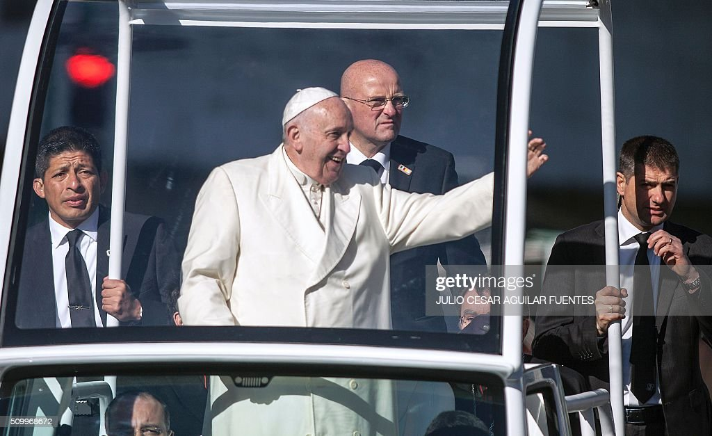 Pope Francis waves from the popemobile on his way to the National Palace, in Mexico City on February 13, 2016. Francis became the first pope to enter Mexico's National Palace to meet President Enrique Pena Nieto, as he starts a cross-country tour that will highlight the country's violence and migration troubles. AFP PHOTO / Julio Cesar Aguilar / AFP / Julio Cesar Aguilar Fuentes