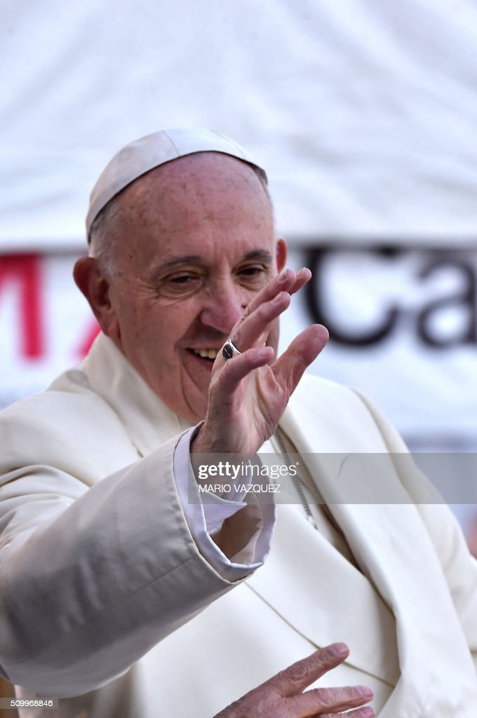 Pope Francis waves from the popemobile on his way to the National Palace, in Mexico City on February 13, 2016. Francis became the first pope to enter Mexico's National Palace to meet President Enrique Pena Nieto, as he starts a cross-country tour that will highlight the country's violence and migration troubles. AFP PHOTO/Mario Vazquez / AFP / MARIO VAZQUEZ