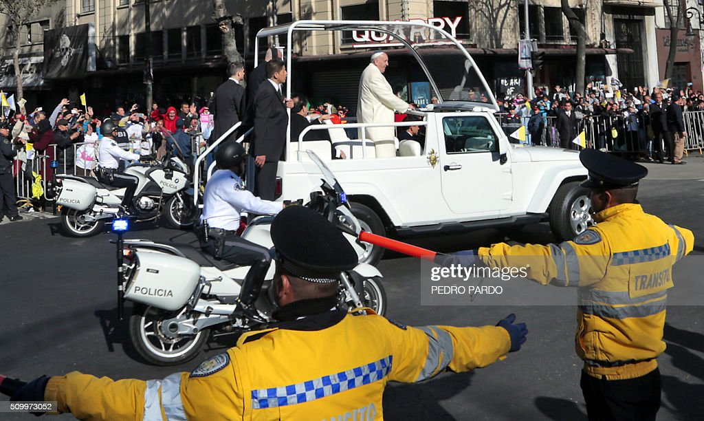 Pope Francis waves from the popemobile on his way to the National Palace, in Mexico City on February 13, 2016. Francis became the first pope to enter Mexico's National Palace to meet President Enrique Pena Nieto, as he starts a cross-country tour that will highlight the country's violence and migration troubles. AFP PHOTO/Pedro Pardo / AFP / Pedro PARDO