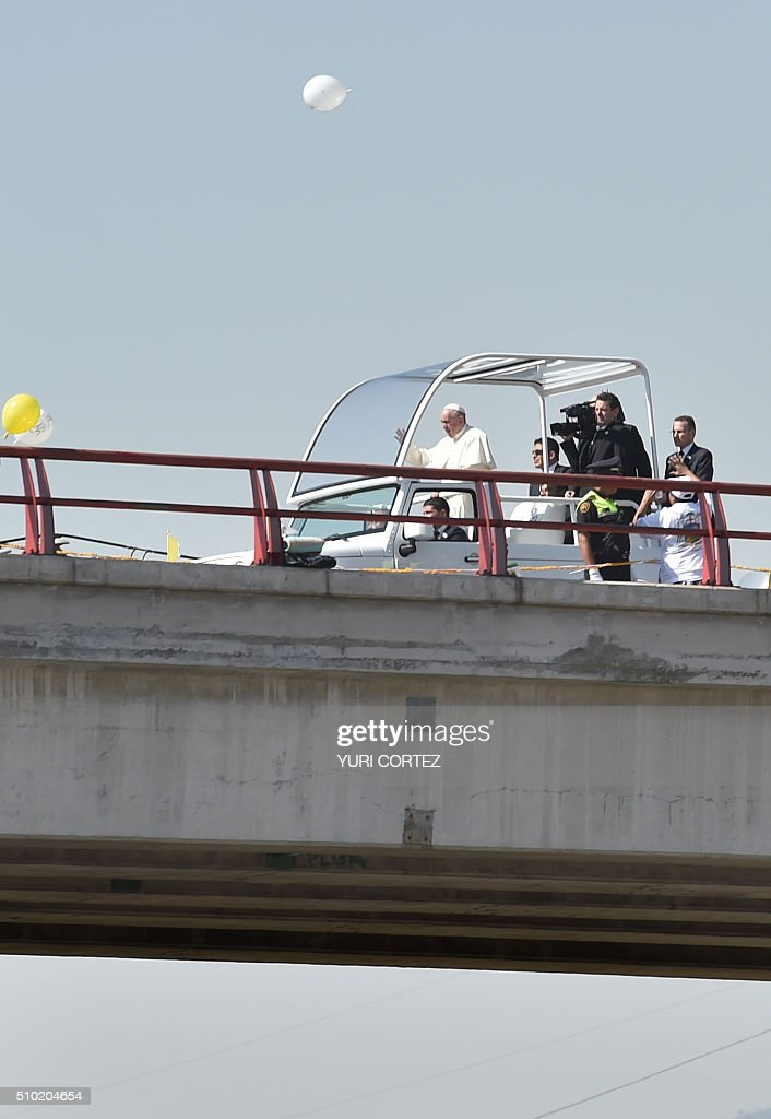 Pope Francis waves from the popemobile upon arrival in Ecatepec --a rough, crime-plagued Mexico City suburb-- where he is to celebrate an open-air mass, on February 14, 2016. Pope Francis has chosen to visit some of Mexico's most troubled regions during his five-day trip to the world's second most populous Catholic country. AFP PHOTO / YURI CORTEZ / AFP / YURI CORTEZ