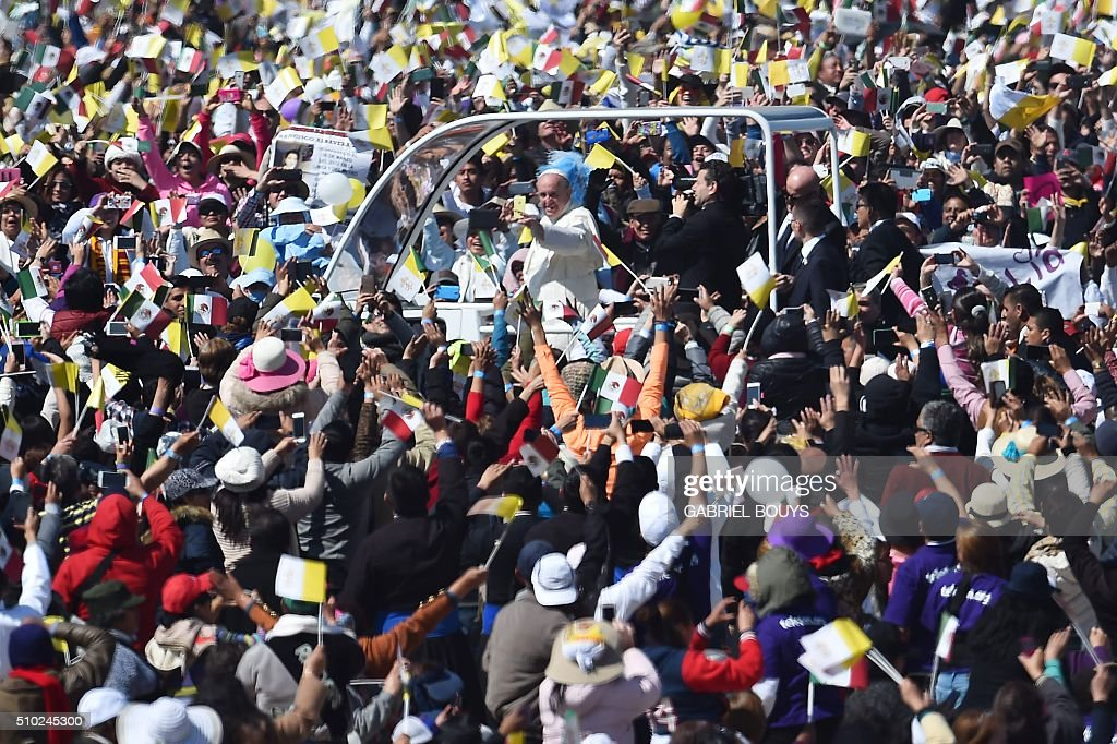 Pope Francis waves from the popemobile upon arrival to celebrate an open-air mass in Ecatepec --a rough, crime-plagued Mexico City suburb-- on February 14, 2016. Pope Francis has chosen to visit some of Mexico's most troubled regions during his five-day trip to the world's second most populous Catholic country. AFP PHOTO/GABRIEL BOUYS / AFP / GABRIEL BOUYS