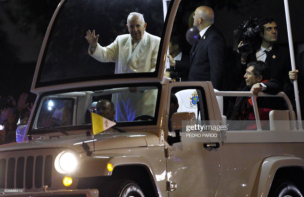 Pope Francis waves from the Popemobile upon his arrival in Mexico City on February 12, 2016. Catholic faithful flocked to the streets of Mexico City to greet Pope Francis on Friday after the pontiff held a historic meeting with the head of the Russian Orthodox Church in Cuba. AFP PHOTO/Pedro Pardo / AFP / Pedro PARDO