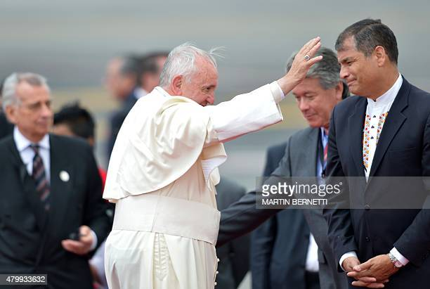 Pope Francis waves next to Ecuadorean President Rafael Correa at the airport in Quito before his departure for Bolivia on July 8 2015 Pope Francis...
