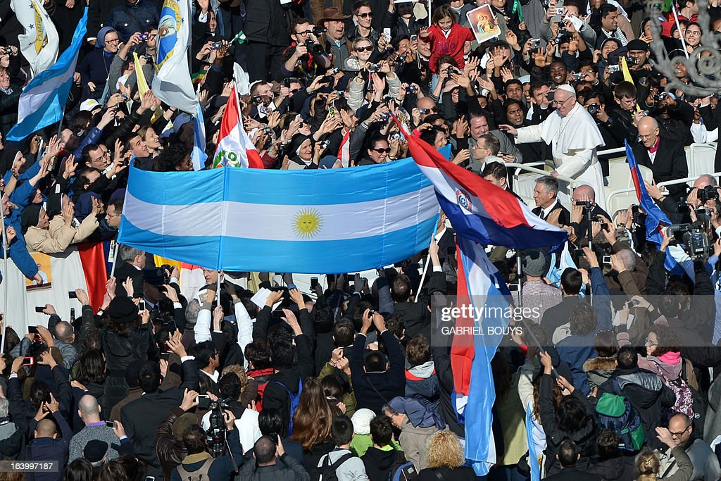 Pope Francis waves past an Argentinian flag as he arrives in the papamobile on St Peter's square for his grandiose inauguration mass on March 19, 2013 at the Vatican.