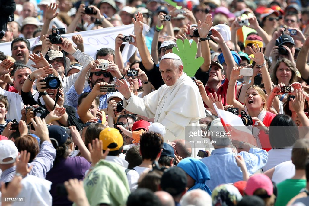 Pope Francis waves to faithful as he arrives in St. Peter's Square for his Weekly Audience on May 1, 2013 in Vatican City, Vatican. Marking the feast of St Joseph the Worker and World Labor Day today, the Pontiff launched an urgent appeal to Christians and men and women of goodwill worldwide to take decisive steps to end slave labor.
