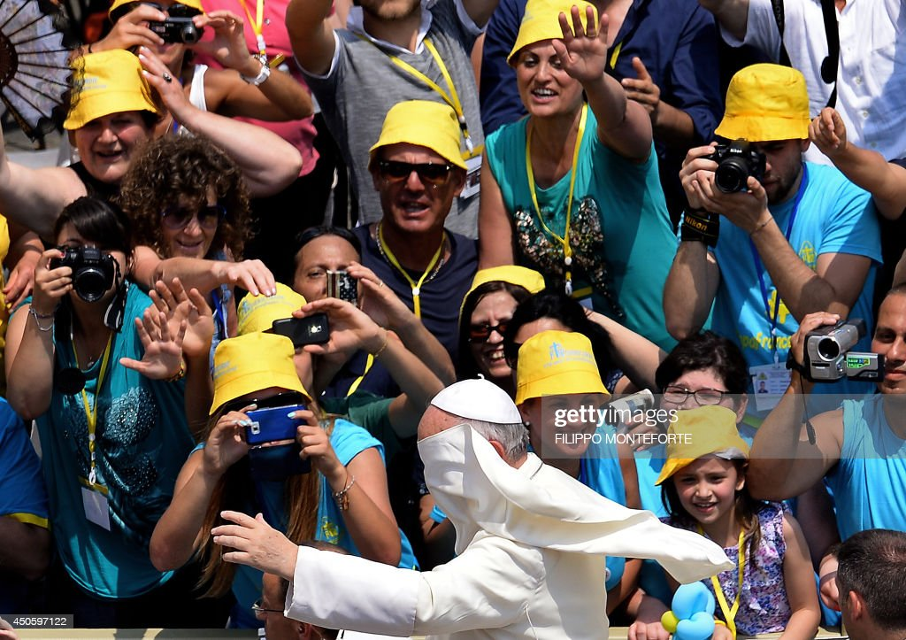 Pope Francis waves to faithfulls as he arrives to lead an audience to catholic volunteers of Misericordie d'Italia in St.Peter's Square at the Vatican on June 14, 2014. AFP PHOTO / Filippo MONTEFORTE
