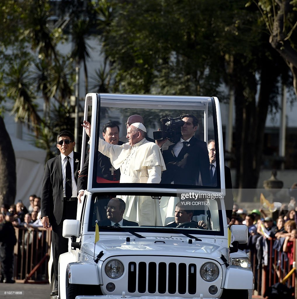Pope Francis waves to people gathered at the Angel of Independence square on February 14, 2016 in Mexico City. The pope urged Mexicans on Sunday to turn their country into a land of opportunity where there is no need to emigrate or mourn victims 'of the merchants of death.' AFP PHOTO/ Yuri CORTEZ / AFP / YURI CORTEZ