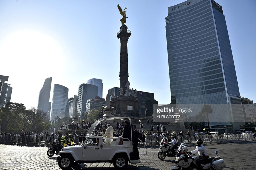 Pope Francis waves to people in the Angel of Independence square on February 14, 2016 in Mexico City. The pope urged Mexicans on Sunday to turn their country into a land of opportunity where there is no need to emigrate or mourn the victims 'of the merchants of death.' AFP PHOTO/ Yuri CORTEZ / AFP / YURI CORTEZ