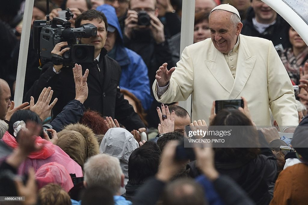 Pope Francis waves to pilgrims gathered at Saint Peter's square in the Vatican, upon his arrival to lead the general weekly audience on February 5, 2014.