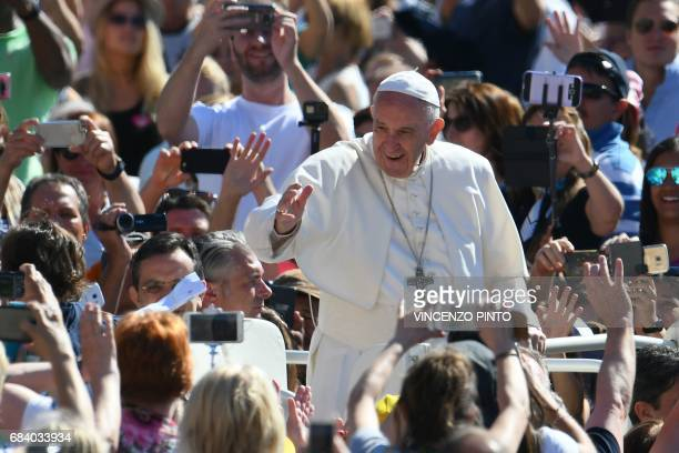 Pope Francis waves to the crowd as he arrives for a weekly general audience at St Peter's square on May 17 2017 in Vatican / AFP PHOTO / Vincenzo...